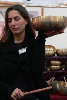 Eva Nerger-Bargellini lauscht einer großen Peter Hess® Sangha-Klangschale auf der Infa 2013